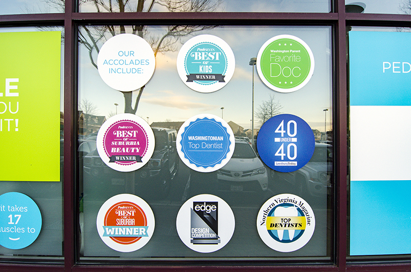 costa family and cosmetic dentistry accolades posted on a window outisde